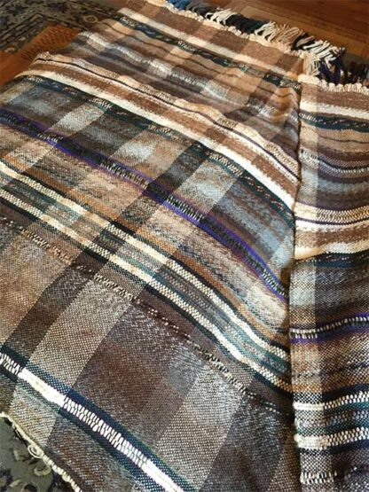 Small, square alpaca fiber blanket in desert colors accented with purple