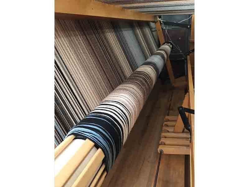 After tying on, the warp is rolled on under tension, with wooden warp slats inserted to prevent the strands from wrapping unevenly. I love the look of a beamed warp!
