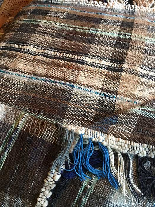 The blanket and fringe both contain soft browns, tans, beige, and cream colors accented with muted aqua and blues